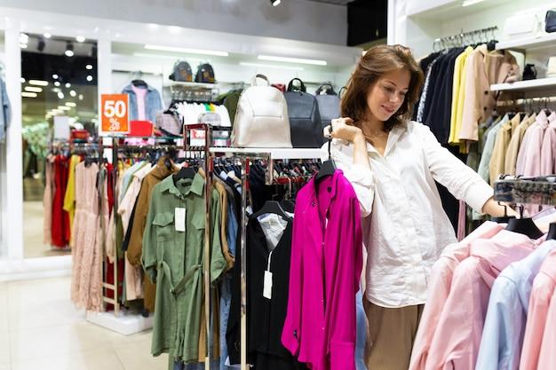 Piękna kaukaski kobieta z krótkimi brązowymi włosami wybiera sukienki w centrum handlowym