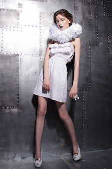 Piękna kaukaski młoda ekstrawagancka młoda kobieta pozuje w białej sukni z dziwnym kołnierzem na metalowej ścianie.