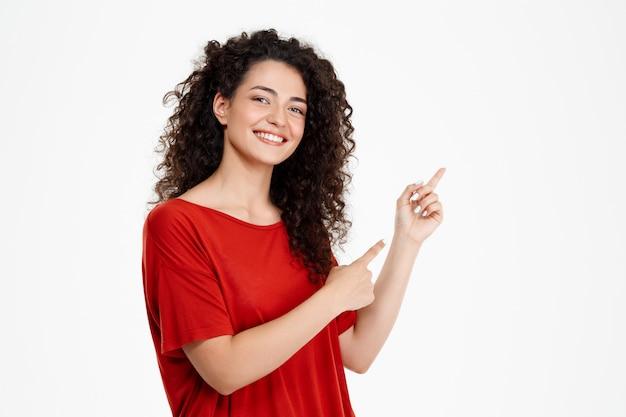 Piękna kędzierzawa dziewczyna wskazuje palec