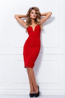 Piękna kędzierzawa kobieta w czerwieni sukni
