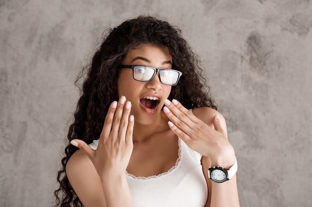 Piękna kędzierzawa latynoska kobieta dyszy śmiechem w szkłach