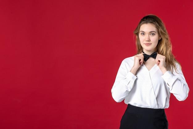 Piękna kelnerka motyl na szyi i stojąca na czerwonym tle