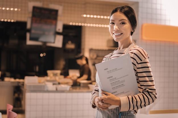 Piękna kelnerka. przyjemna piękna młoda kobieta ubrana w pasiastą koszulę pracująca jako kelnerka w przytulnej stołówce