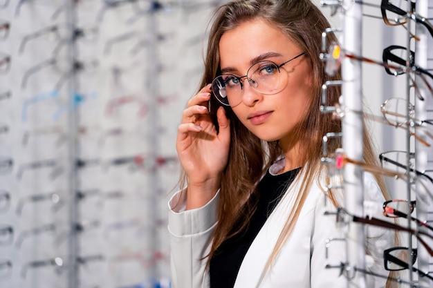 Piękna klientka lub optyk stoi z surowymi okularami w sklepie optycznym