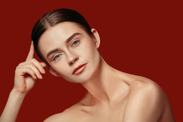 Piękna kobieca twarz. doskonała i czysta skóra młodej kobiety rasy kaukaskiej na czerwonym studio.