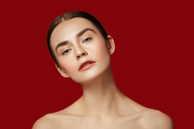 Piękna kobieca twarz. doskonała i czysta skóra młodej kobiety rasy kaukaskiej na tle czerwonego studia.