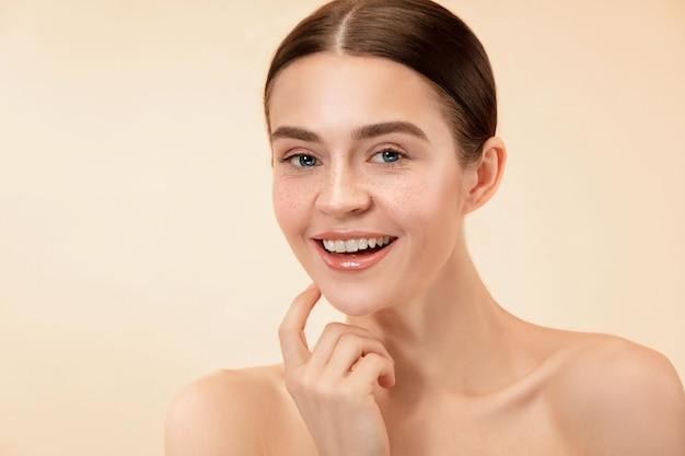 Piękna kobieca twarz. idealna i czysta skóra młodej kobiety rasy kaukaskiej na pastelowym tle studia.