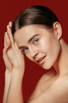 Piękna kobieca twarz. idealna i czysta skóra młodej kobiety rasy kaukaskiej na tle czerwonego studia.
