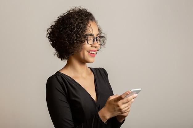Piękna kobieta afro uśmiecha się, w okularach i przy użyciu smartfona
