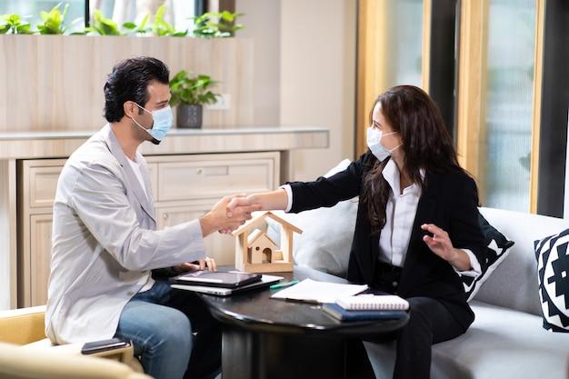 Piękna kobieta agent nieruchomości oferująca i pokazująca prezentację online na laptopie w biurze dla przystojnego mężczyzny. osoby noszące maskę ochronną na twarz przed wirusem koronowym.