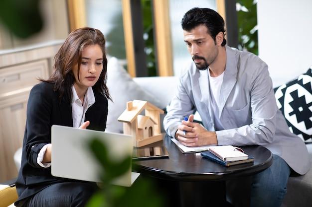 Piękna kobieta agent nieruchomości oferująca i pokazująca prezentację online na laptopie w biurze dla przystojnego mężczyzny.