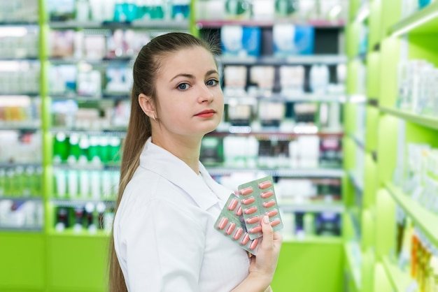 Piękna kobieta aptekarz pokazuje niektóre tabletki w blistrze
