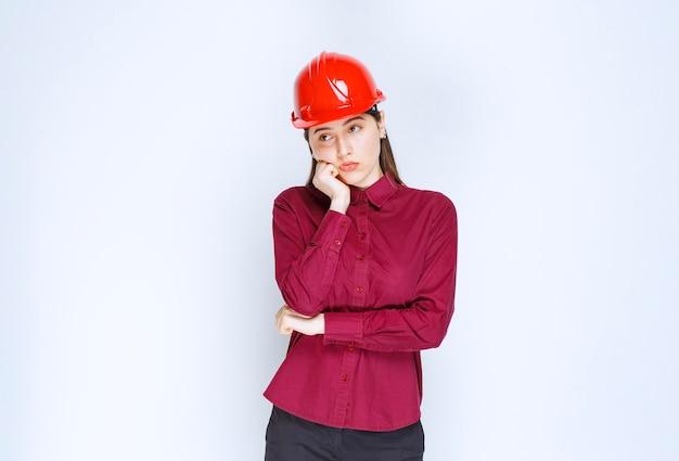 Piękna kobieta architekt w czerwonym kasku stoi i ciężko myśli.
