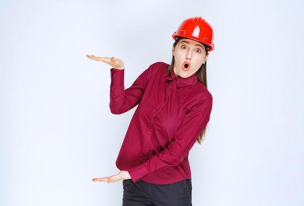 Piękna kobieta architekt w czerwonym kasku stojąc i trzymając otwartą przestrzeń.