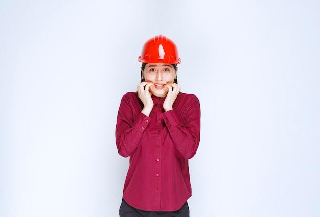 Piękna kobieta architekt w czerwonym kasku twardym boi się czegoś.