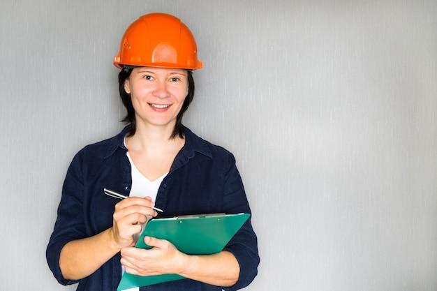 Piękna kobieta architekt w twardy kapelusz z notatkami i piórem na szaro