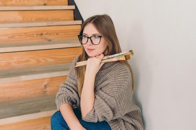 Piękna kobieta artystka w okularach i casual, siedząca na schodach ze szczotkami