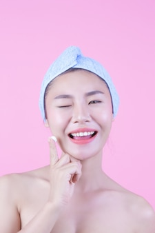 Piękna kobieta asia myje jej twarz na różowym tle.