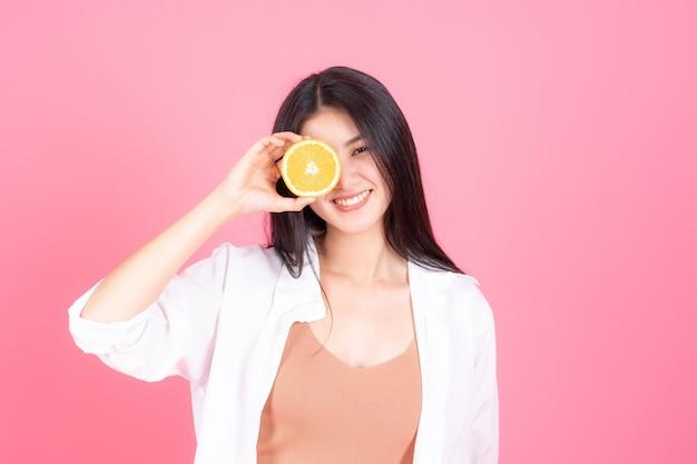 Piękna kobieta azjatycka śliczna dziewczyna czuje szczęśliwego holdind pomarańczowego owoc dla dobrego zdrowia na różowym tle