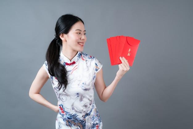 Piękna kobieta azjatyckich nosić chiński tradycyjny strój z czerwoną kopertą lub czerwoną paczką
