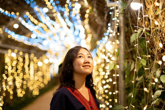 Piękna kobieta azjatycko-tajska w tradycyjnej północno-tajskiej sukni pozuje do fotografii w festiwalu z piękną oświetleniową ścianą bokeh.