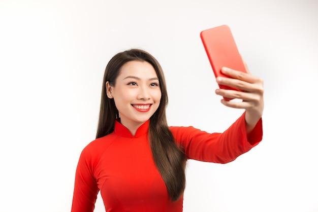 Piękna kobieta azji biorąc selfie z jej telefonem na białym.