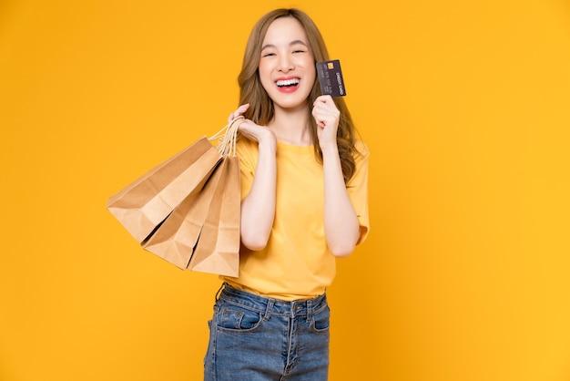 Piękna kobieta azji gospodarstwa brązowy puste rzemiosło papierowe torby na zakupy i pokazując kartę kredytową na żółtym tle.
