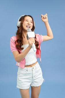 Piękna kobieta azji śpiewa karaoke na białym tle na niebieskim tle.