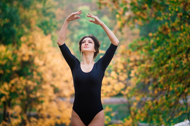 Piękna kobieta, baletnica, lekkoatletka w czarnym body trenuje w parku