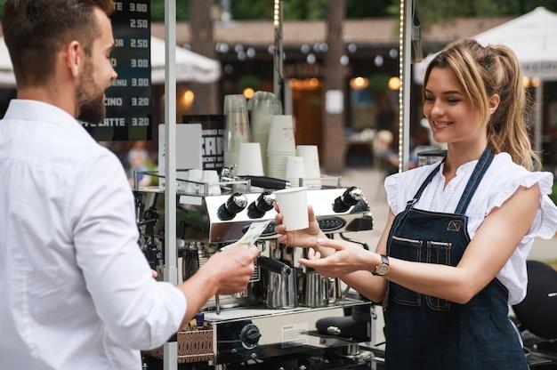 Piękna kobieta barista sprzedaje kawę klientowi w kawiarni ulicy