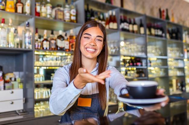 Piękna kobieta barista trzyma kubek z gorącą kawą, patrząc na kamery i uśmiechając się stojąc w pobliżu kontuaru barowego w kawiarni