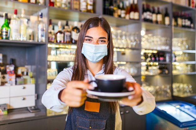 Piękna kobieta-barista trzyma kubek z gorącą kawą, patrzy w kamerę i nosi ochronną maskę na twarz, stojąc w pobliżu kontuaru barowego w kawiarni