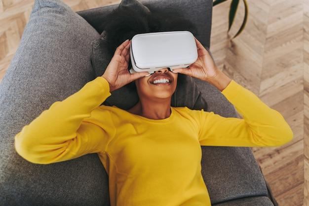 Piękna kobieta bawiąca się w domu z goglami vr - czarna kobieta leżąca na kanapie podczas interakcji z technologią rozszerzonej rzeczywistości