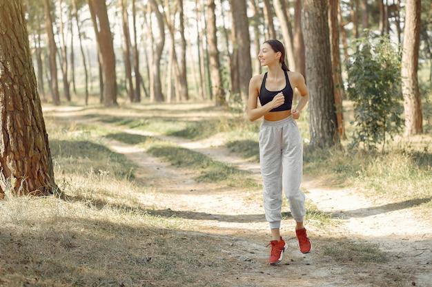Piękna kobieta biega w lato parku