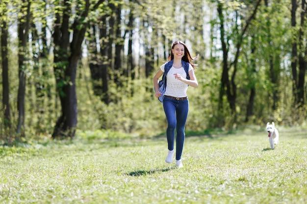 Piękna kobieta biegnie z psem w letnim parku