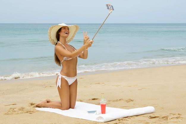 Piękna kobieta bierze selfie na plaży