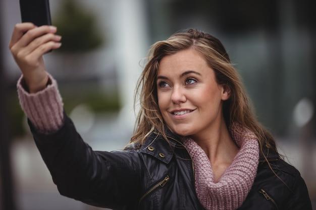 Piękna kobieta bierze selfie na smartphone