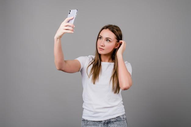 Piękna kobieta bierze selfie na telefonie na szarym tle