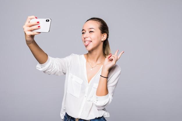 Piękna kobieta, biorąc selfie i pokazując znak zwycięstwa z doskonałym uśmiechem na białym tle na szarej ścianie