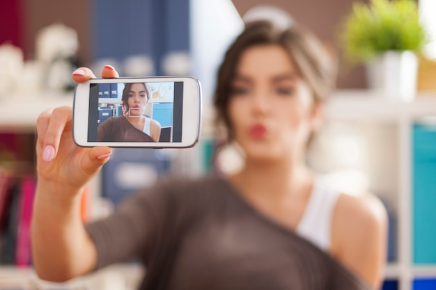 Piękna kobieta, biorąc zdjęcie selfie z dmuchaniem buziaków