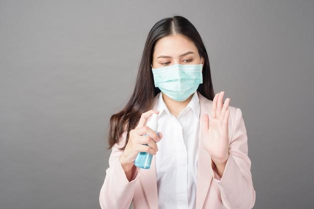 Piękna kobieta biznesu używa sprayu z alkoholem do profilaktyki covid-19