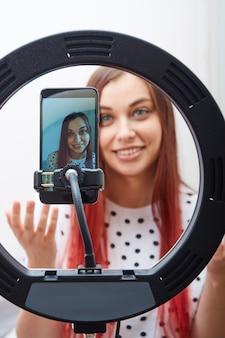 Piękna kobieta blogerka w białej koszulce w kropki prowadzi transmisję na żywo za pomocą nowoczesnego smartfona, lampy pierścieniowej. skoncentruj się na smartfonie.