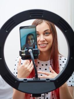 Piękna Kobieta Blogerka W Białej Koszulce W Kropki Prowadzi Transmisję Na żywo Za Pomocą Nowoczesnego Smartfona, Lampy Pierścieniowej. Premium Zdjęcia