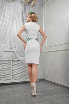 Piękna kobieta, blond dziewczyna w krótkiej białej sukni na obcasach,