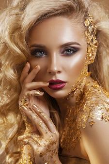 Piękna kobieta, blond włosy, profesjonalny makijaż, złoty kolor.