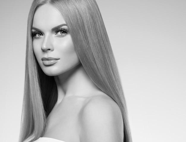 Piękna kobieta blond z długimi włosami naturalny makijaż i koncepcja kosmetyczna zdrowej skóry. strzał studio. monochromia. szary. czarny i biały. strzał studio.