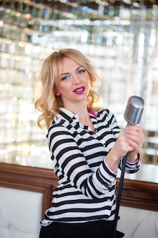 Piękna kobieta, blondynka, mikrofon. śpiew, piękny uśmiech