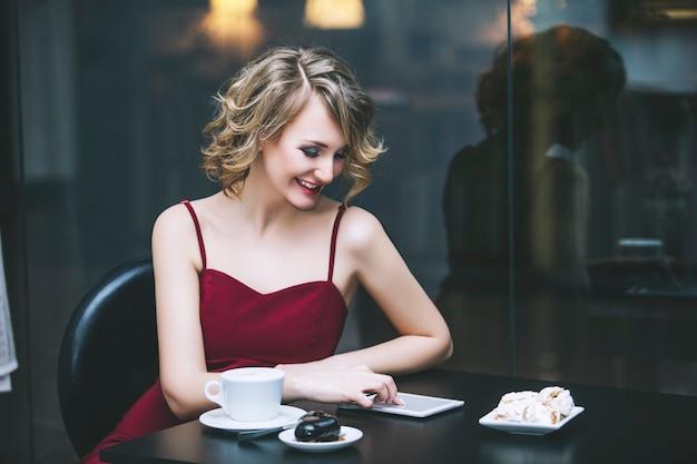 Piękna kobieta blondynka model w czerwonym kombinezonie modnym i eleganckim przy filiżance kawy i tablecie w restauracji