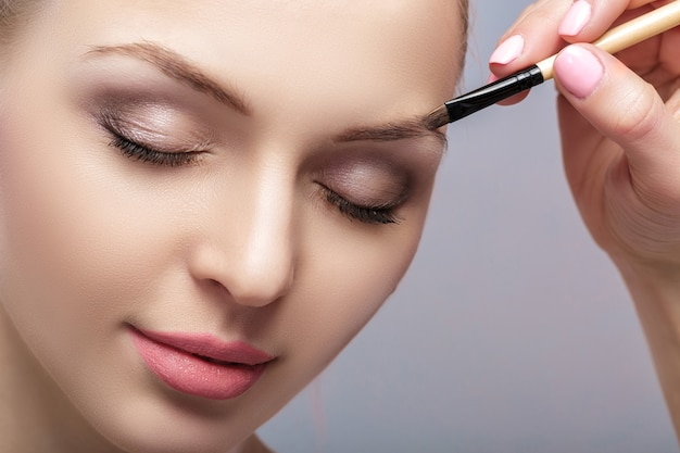 Piękna kobieta blondynka używa profesjonalnego pędzla do makijażu brwi.