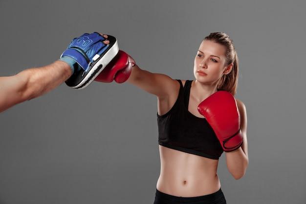 Piękna kobieta boksuje na szarym tle